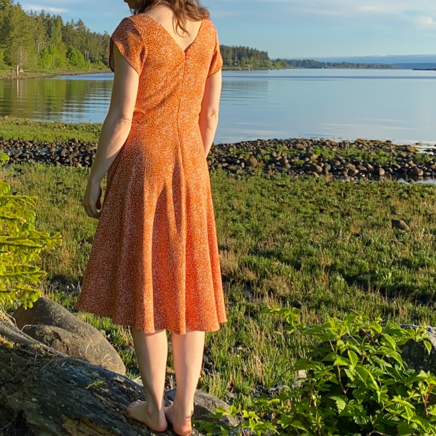 Me standing on a log on the beach with my back to the camera and the water behind me, wearing a orange v-back midi dress with white polka dots