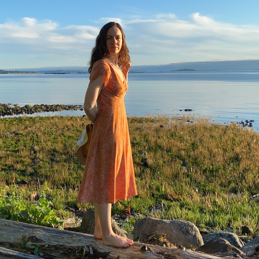 Me standing on a log on the beach with the water behind me, wearing a orange v-neck midi dress