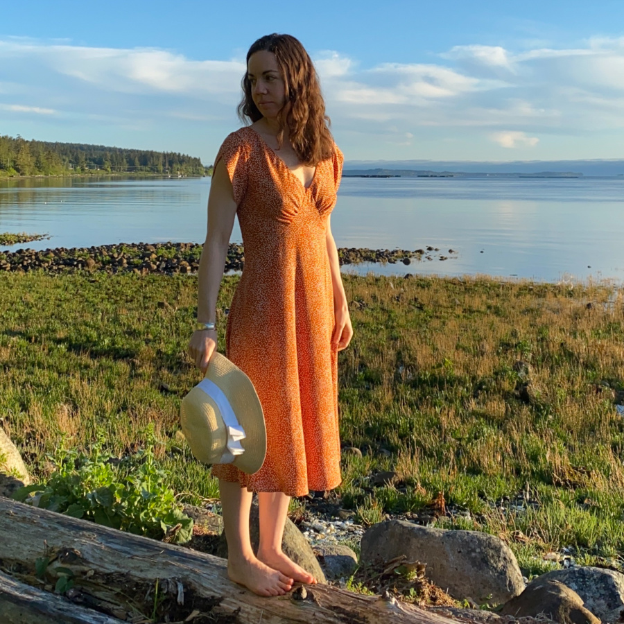 Me standing on a log on the beach with the water behind me, wearing a orange v-neck midi dress with white polka dots