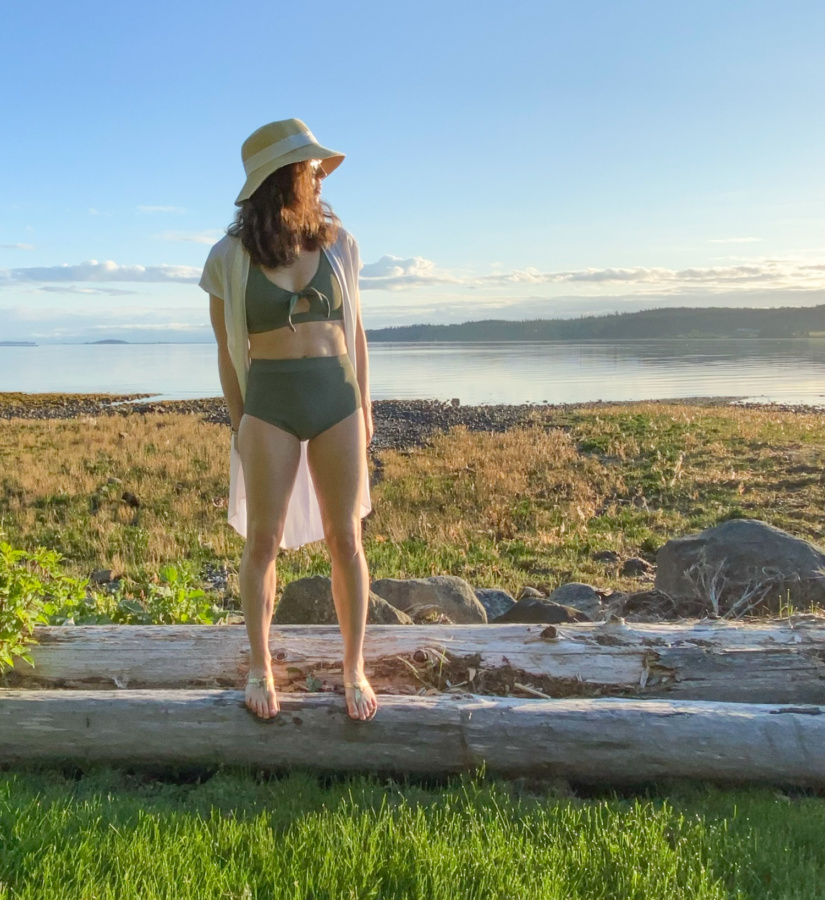 Me standing on a log in front of a rocky beach wearing a sage green swim suit, white coverup and a hat