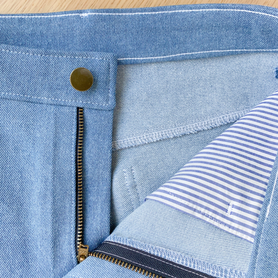 Close up of open front with button, zip and striped pocket bag showing.